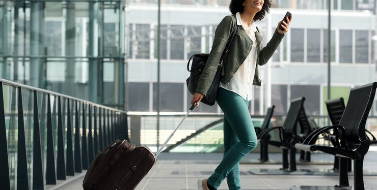 mulher no aeroporto olhando para o celular e carregando sua mala