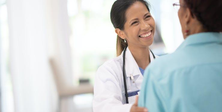 Médica e paciente se cumprimentando