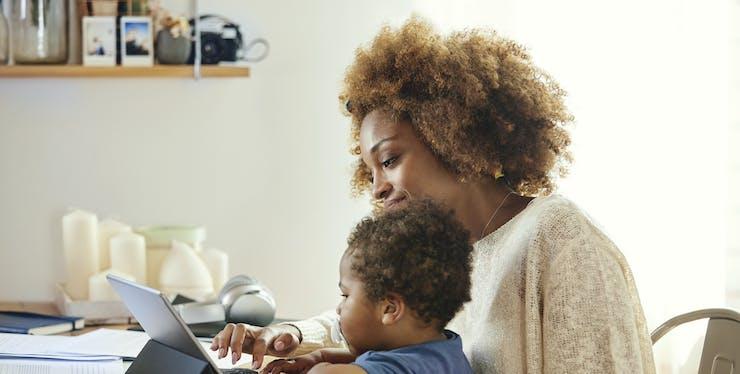 mulher trabalhando com criança no colo