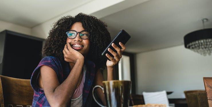mulher jovem sentada na mesa com o celular na mão