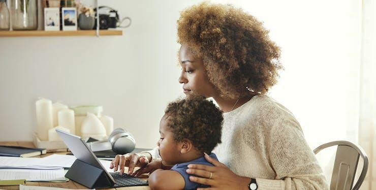 mulher trabalhando com filho no colo