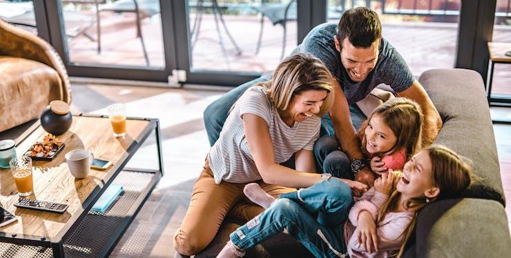 família brincando de cócegas no sofá