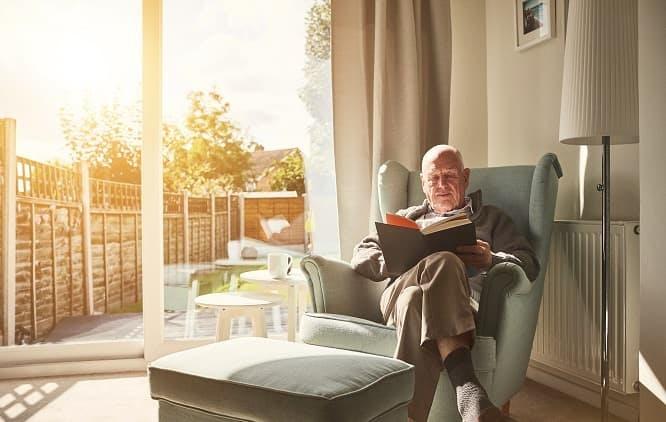 Idoso lendo um livro sentado em uma poltrona