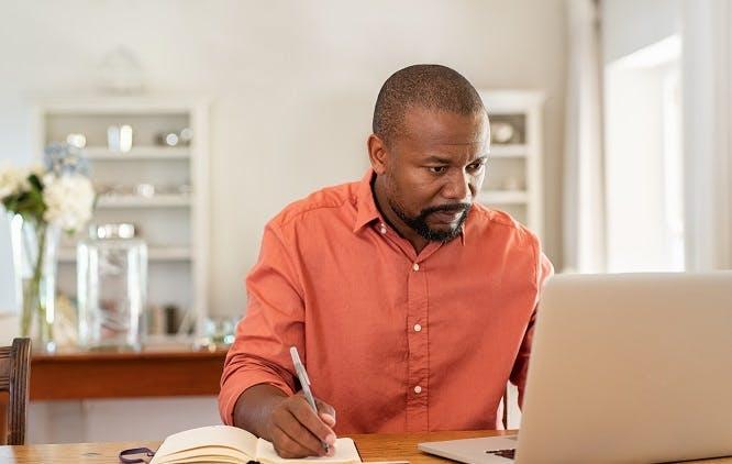 Homem fazendo anotações em um caderno enquanto observa seu computador