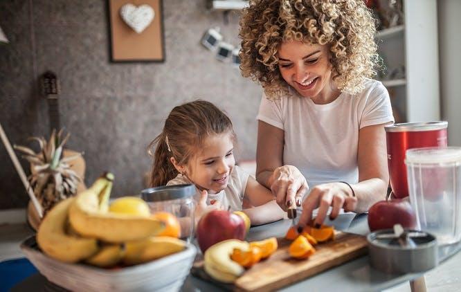 Mãe e filha cortando alimentos na cozinha