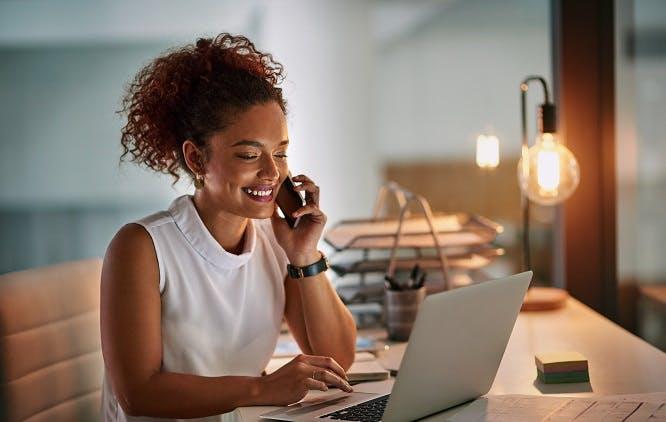 Mulher olhando para o computador, falando no telefone e sorrindo