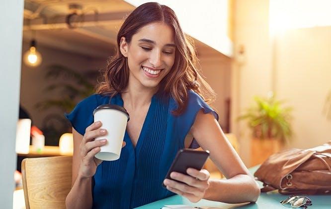 Mulher mexendo no celular enquanto toma café