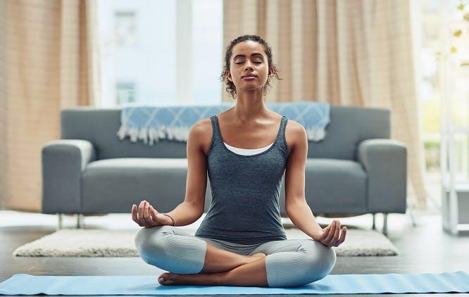 Mulher meditando na sala de casa