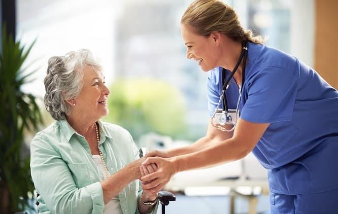 paciente e médica segurando as mãos uma da outra e sorrindo