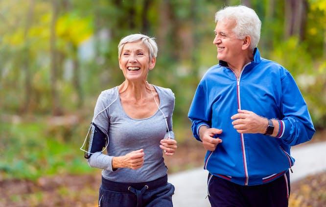 Casal de idosos correndo no parque