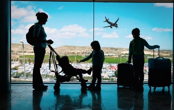 mãe e três filhos em frente à janela de aeroporto esperando avião para viajarem