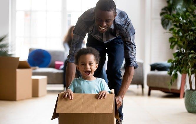 Pai brincando com criança em caixa de papelão