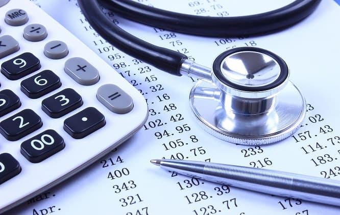 caneta, calculadora e estetoscópio sobre folha com números