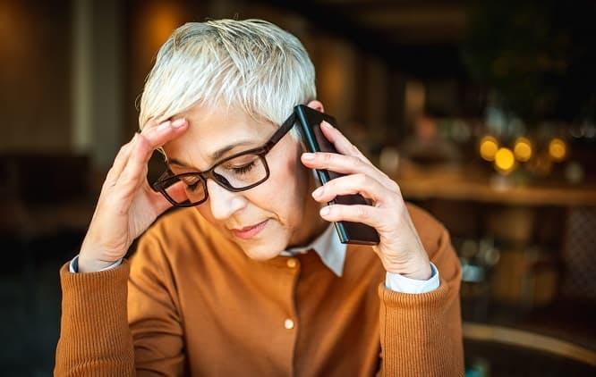 Mulher falando no celular e com expressão preocupada