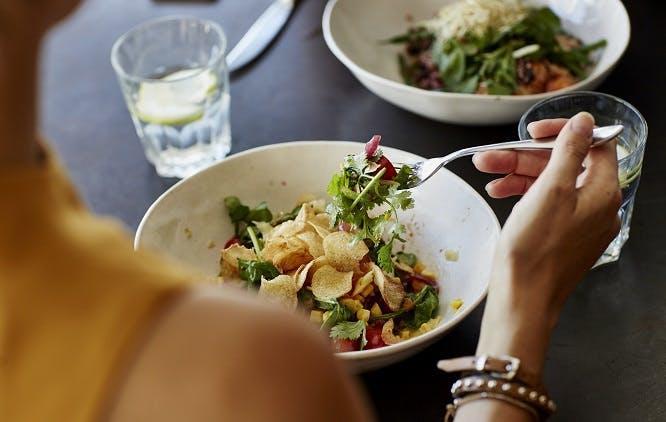 Mulher comendo salada em restaurante