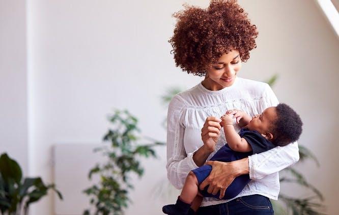 Mãe brincando com bebê no colo