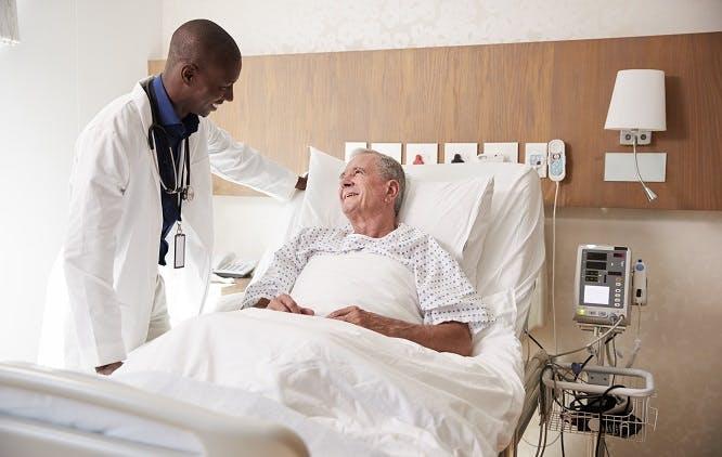 Médico atendendo paciente idoso no quarto de hospital
