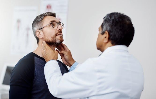 Médico examinando tieóide de paciente