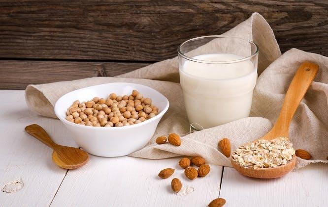 Copo com leite ao lado de amêndoas, aveia e grão de bico - substitutos para pessoas com intolerância à lactose