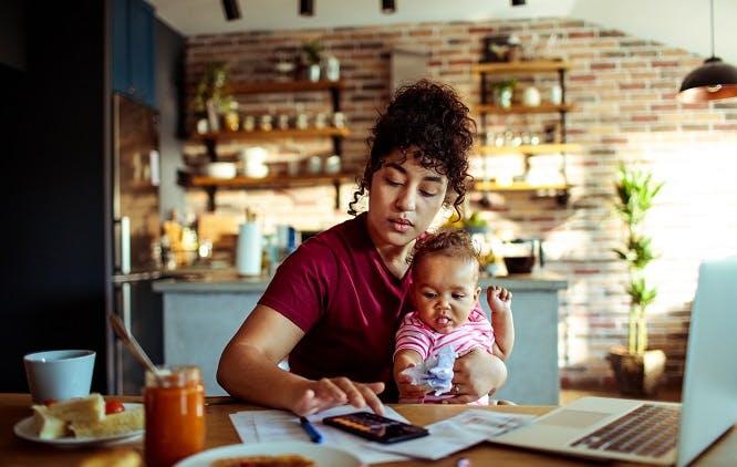 Mãe segurando filha bebê no colo enquanto faz contas na calculadora do celular