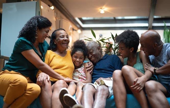 Família sentada em sofá e sorrindo