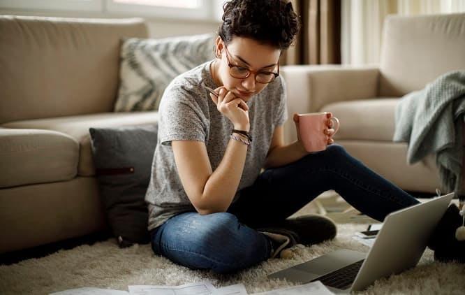 mulher sentada no chão da sala, tomando café e analisando papeis