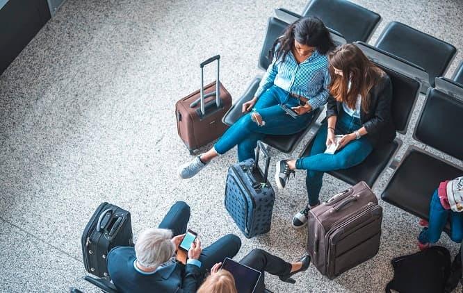 pessoas sentadas na sala de espera do aeroporto com suas malas