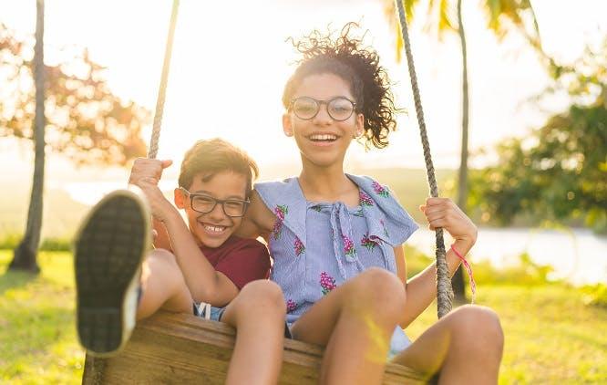 Duas crianças de óculos em um balanço