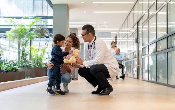 Médico agachado para fica na altura de uma criança que é segurada pela mãe