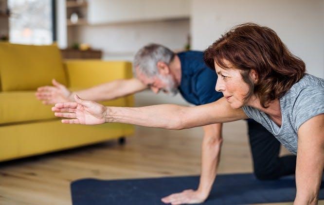 casal fazendo exercícios na sala de casa