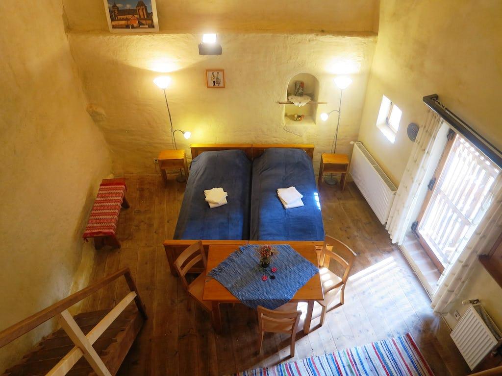 Cameră cu două paturi, masă și zonă de relaxare