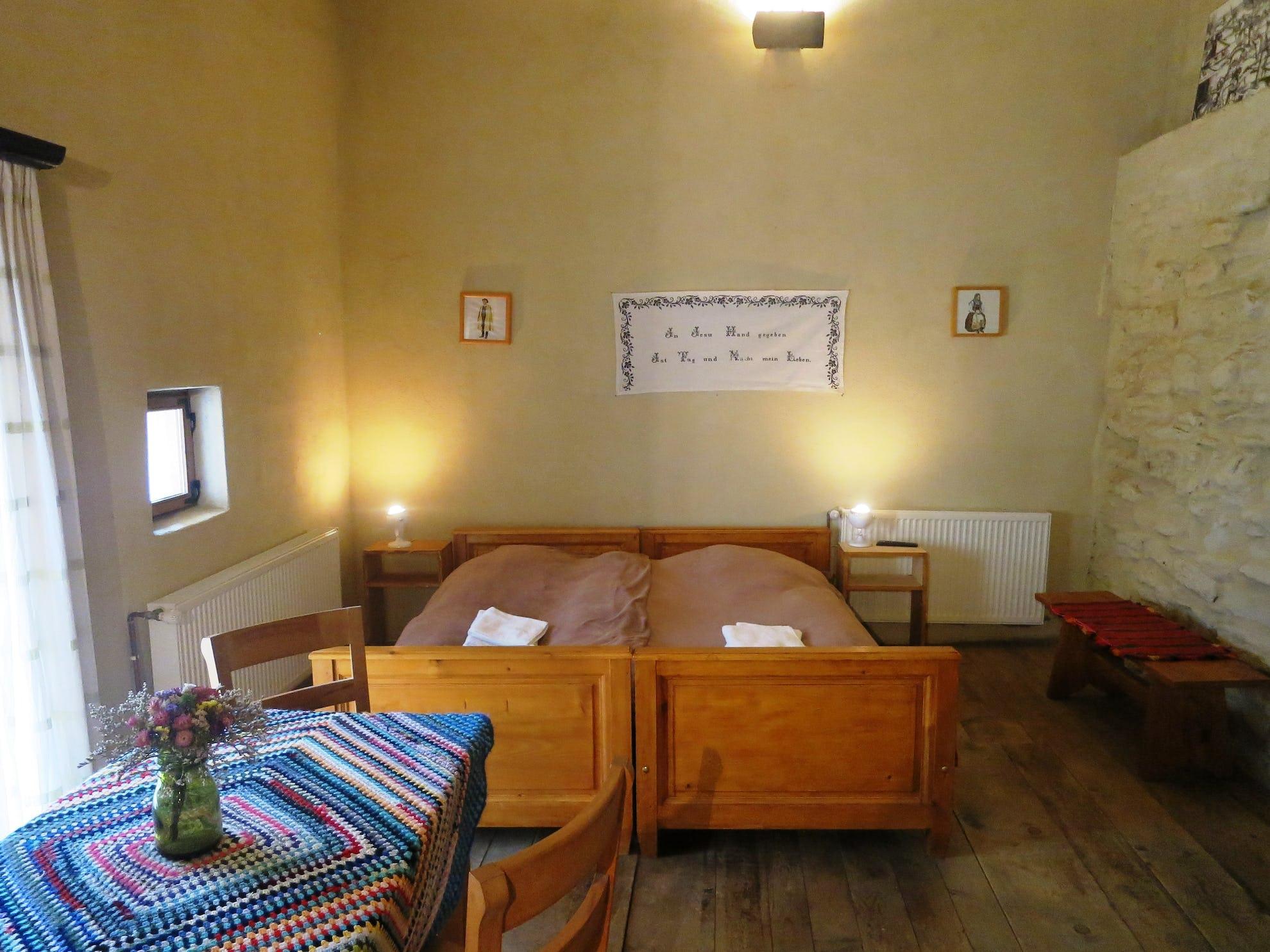 Doua paturi și masă cu vază de flori