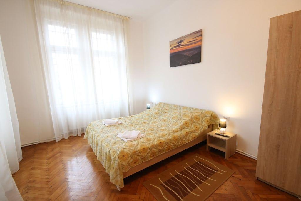 Cameră cu pat în fața ferestrei și tablou pe perete