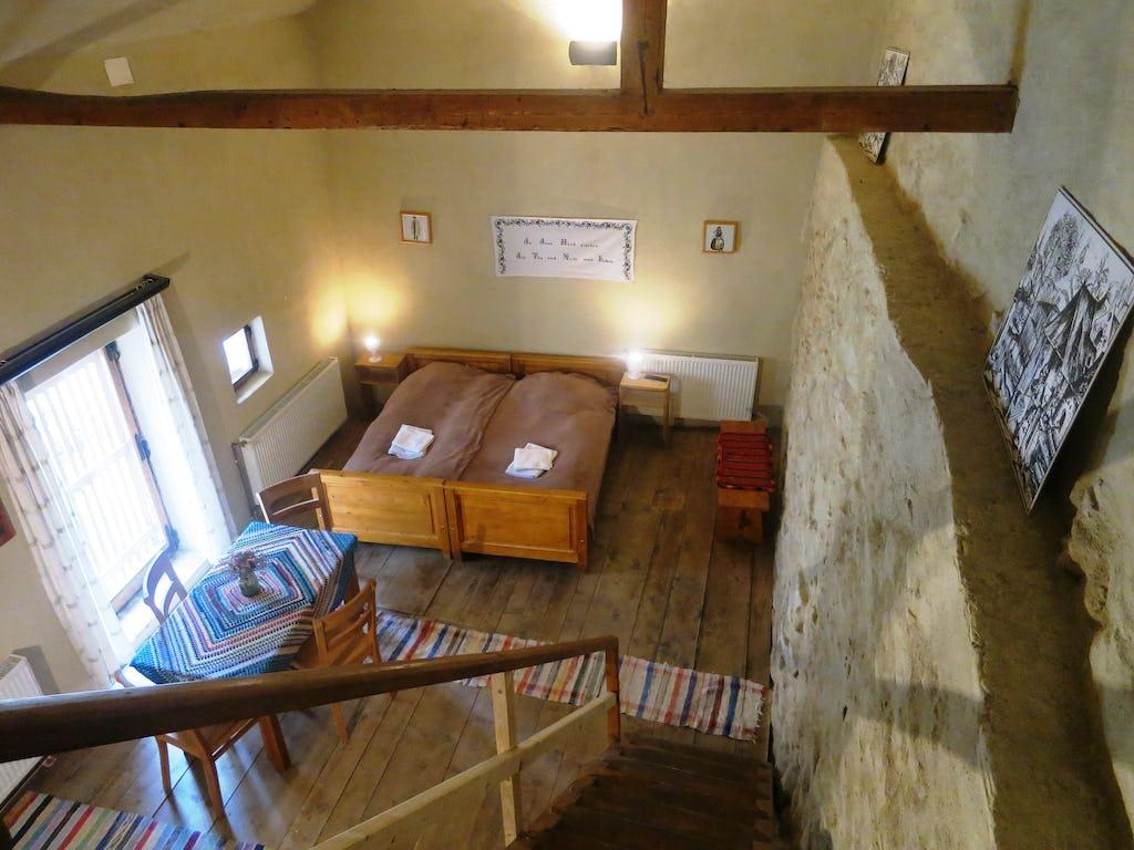 Două paturi, masă și zidul fortificat