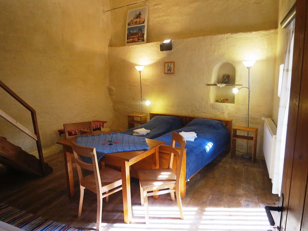 Camera în ansamblu ei cu spațiu de servit masa și paturi de dormit