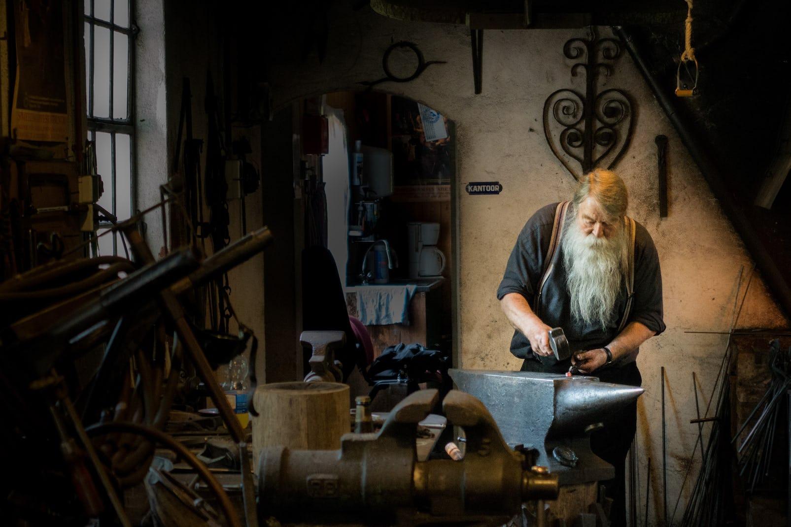Altes Mann arbeitet in mittelalterliches Werkstatt