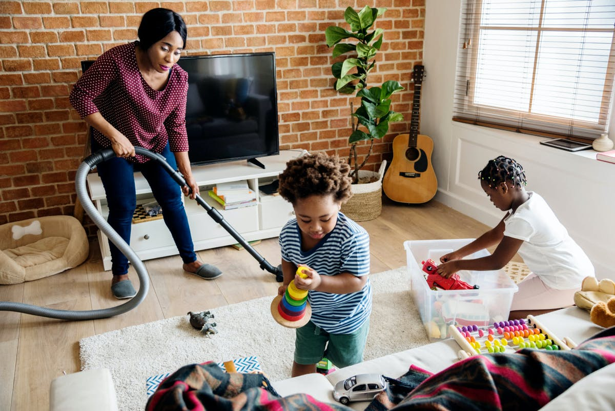 A woman vacuuming the floor while two kids play.