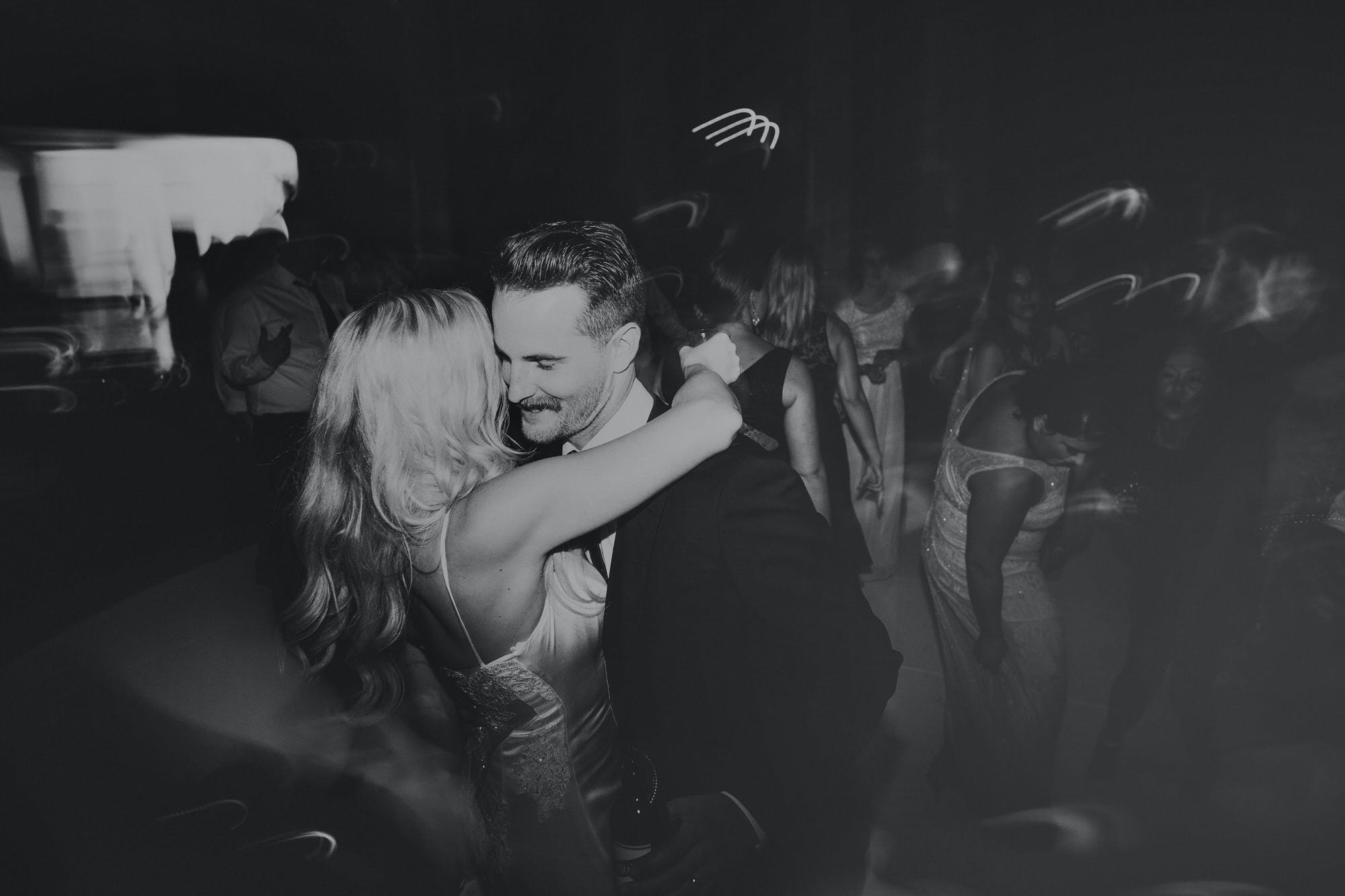 moody black and white couple dancing on wedding night