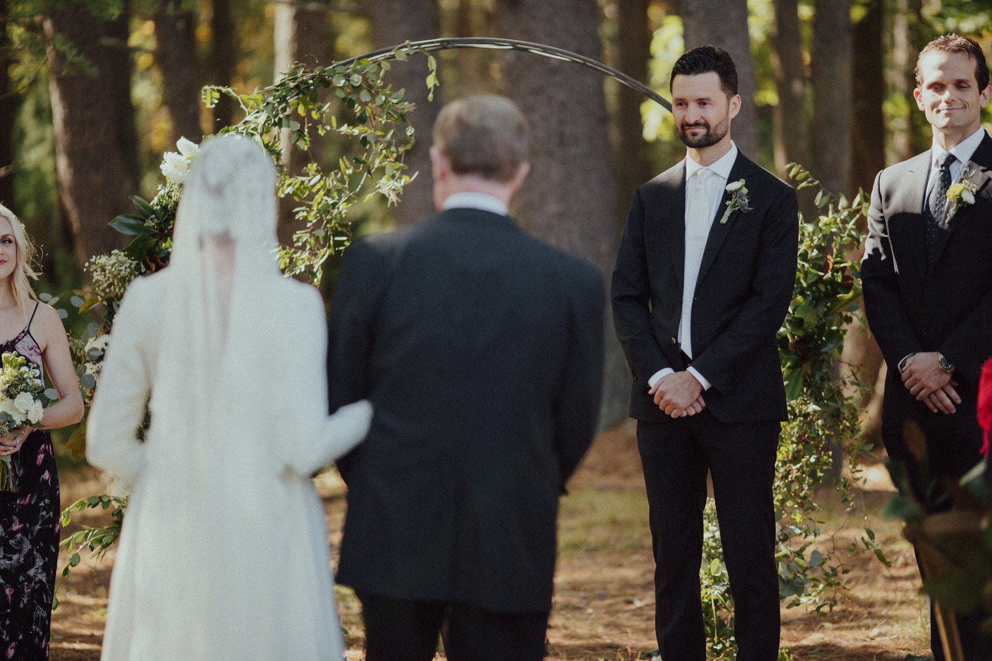 groom crying watching bride walk down the aisle