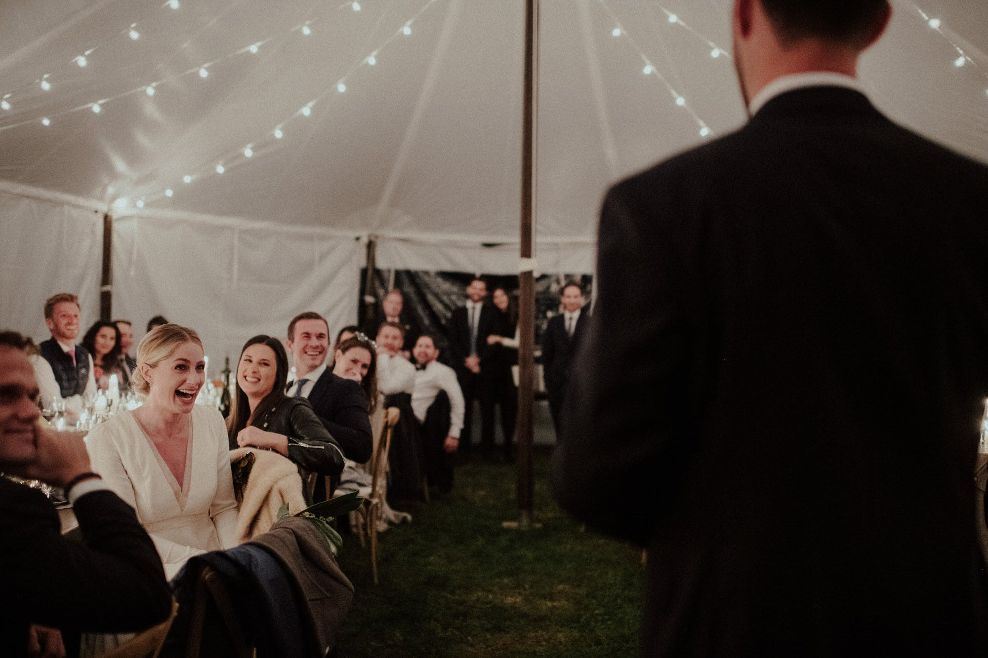 bride candidly laughing at her husband's speech