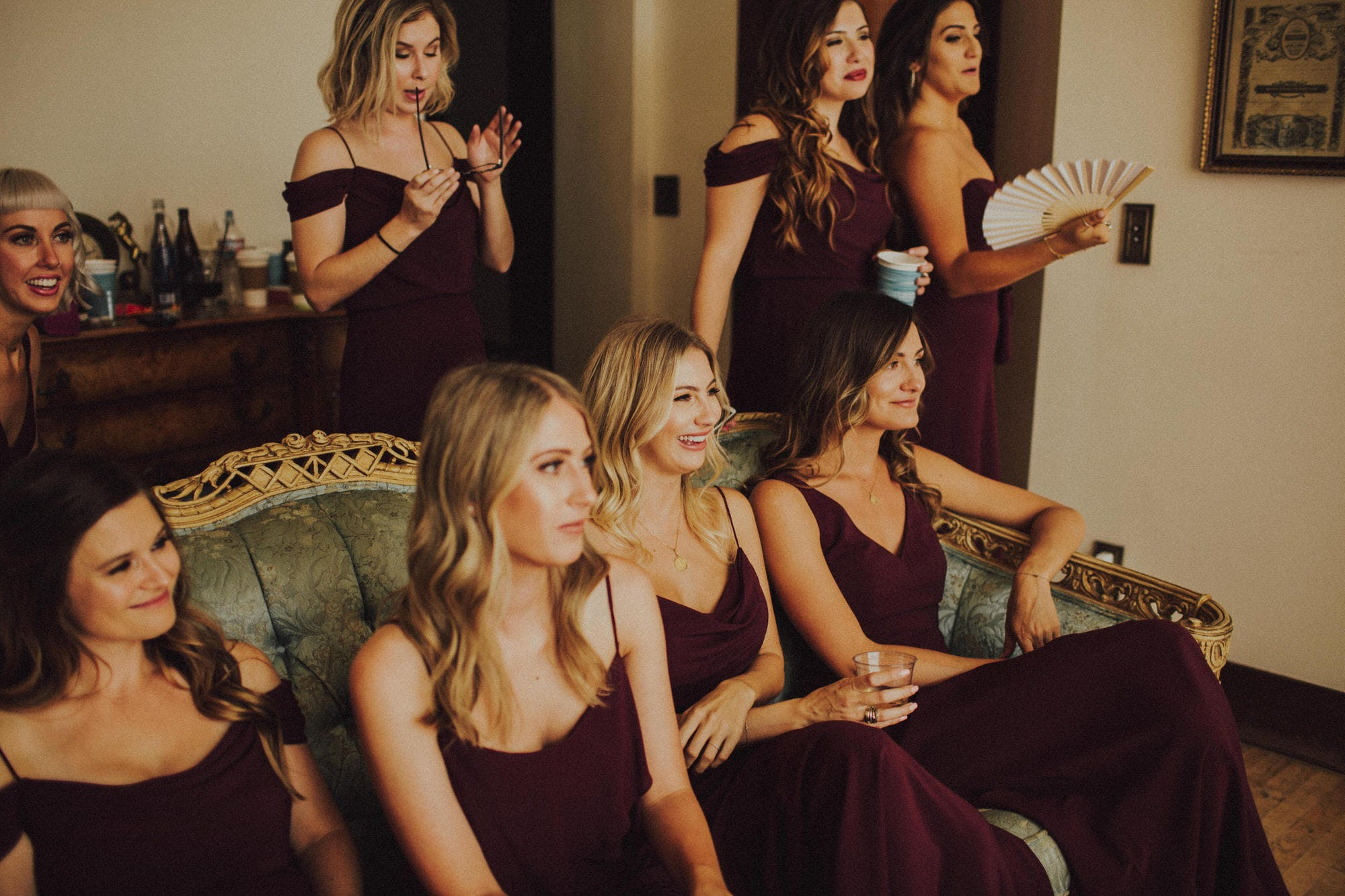 bridesmaids watching bride getting dress on