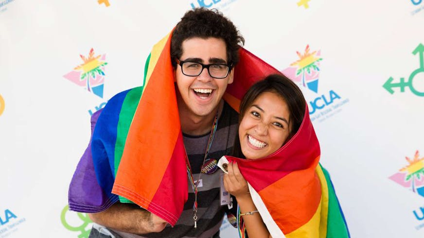 Image of two people inside the LGBTQ rainbow flag.