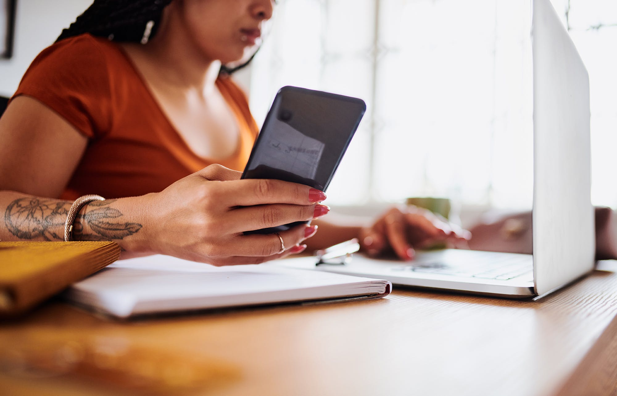 Woman working from home on her laptop and phone