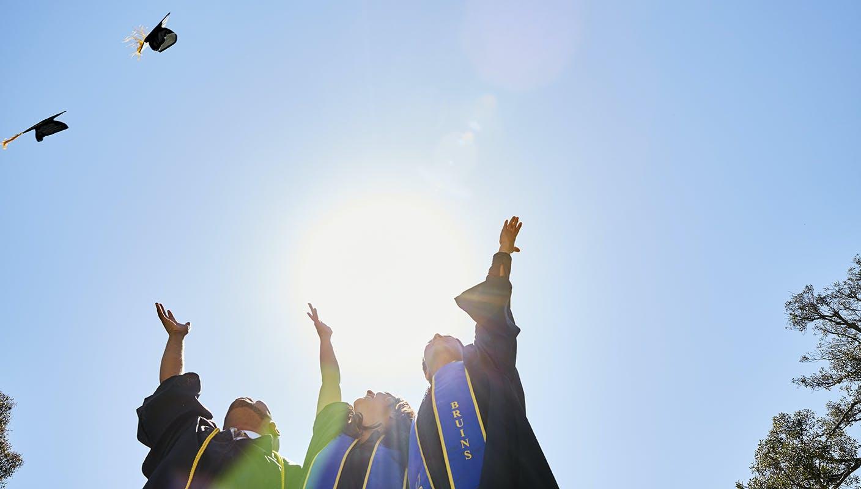 graduating students throwing their graduation hats
