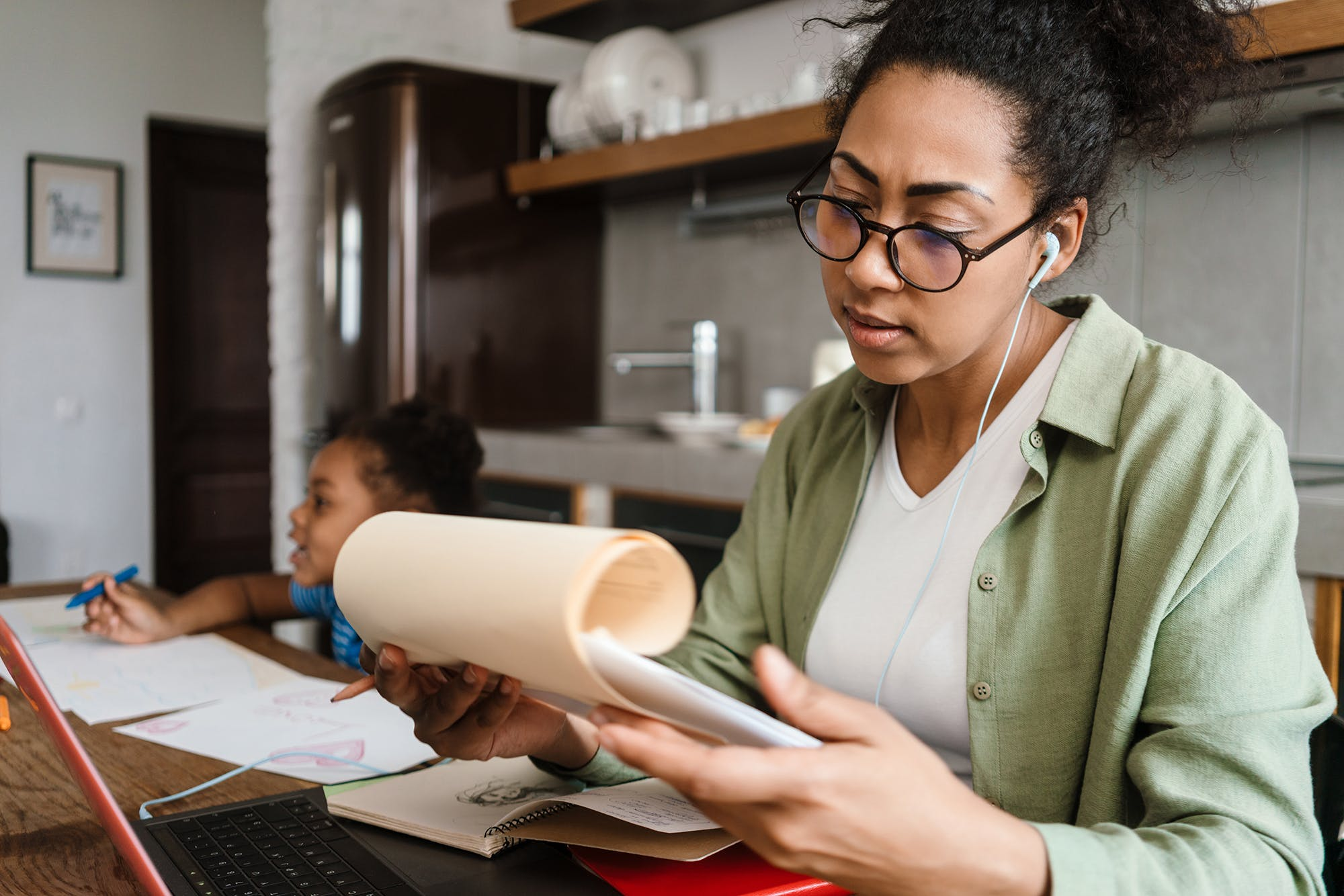 Woman working from home with child in background
