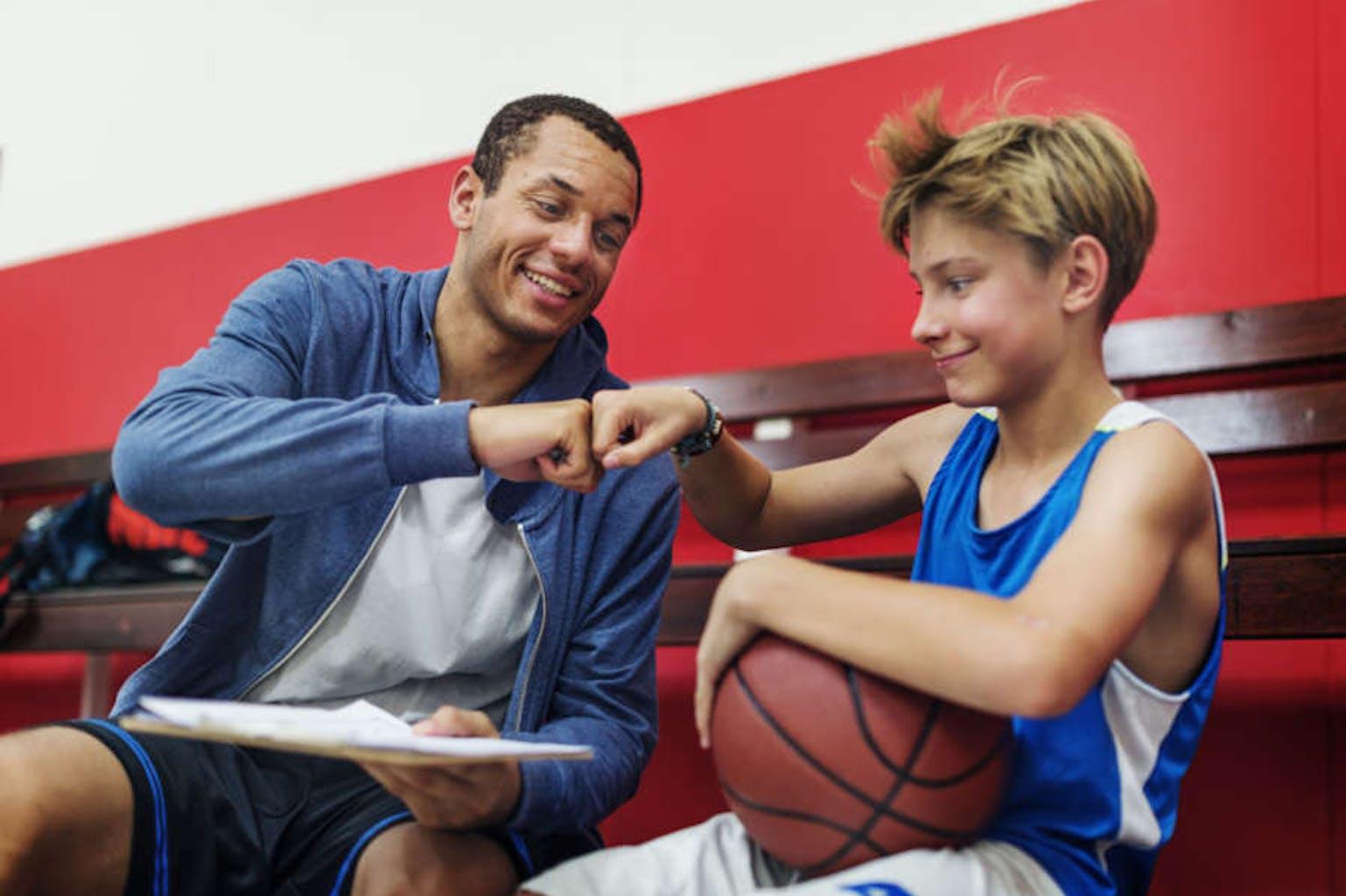 Basketball coach and boy fist bumping