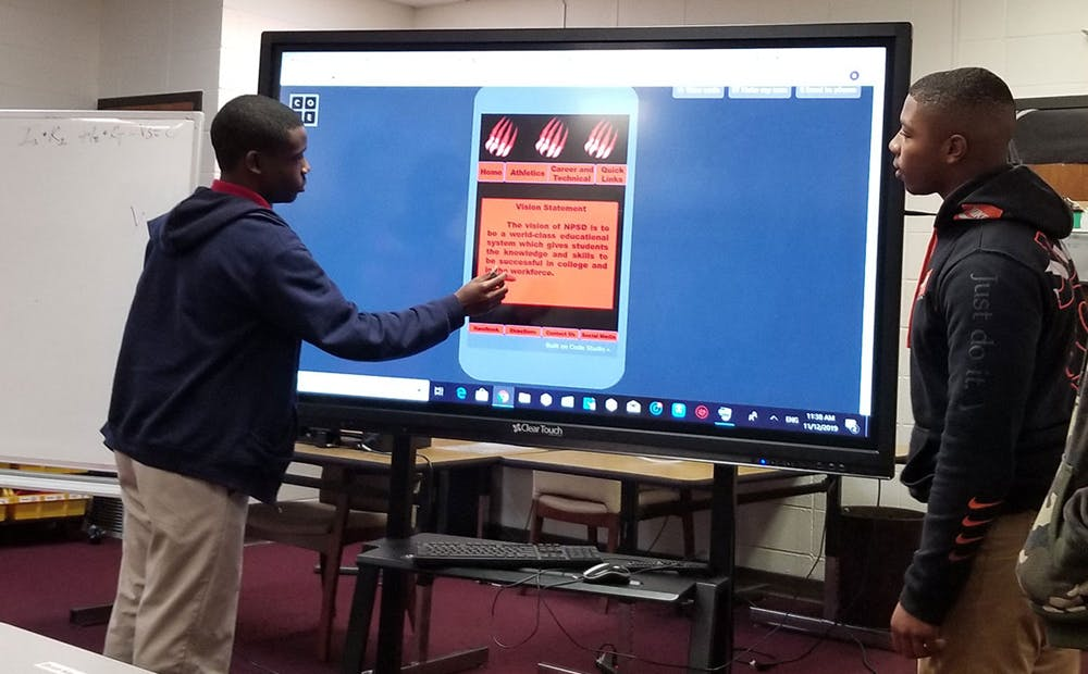 High school students in Mississippi presenting on a smart board