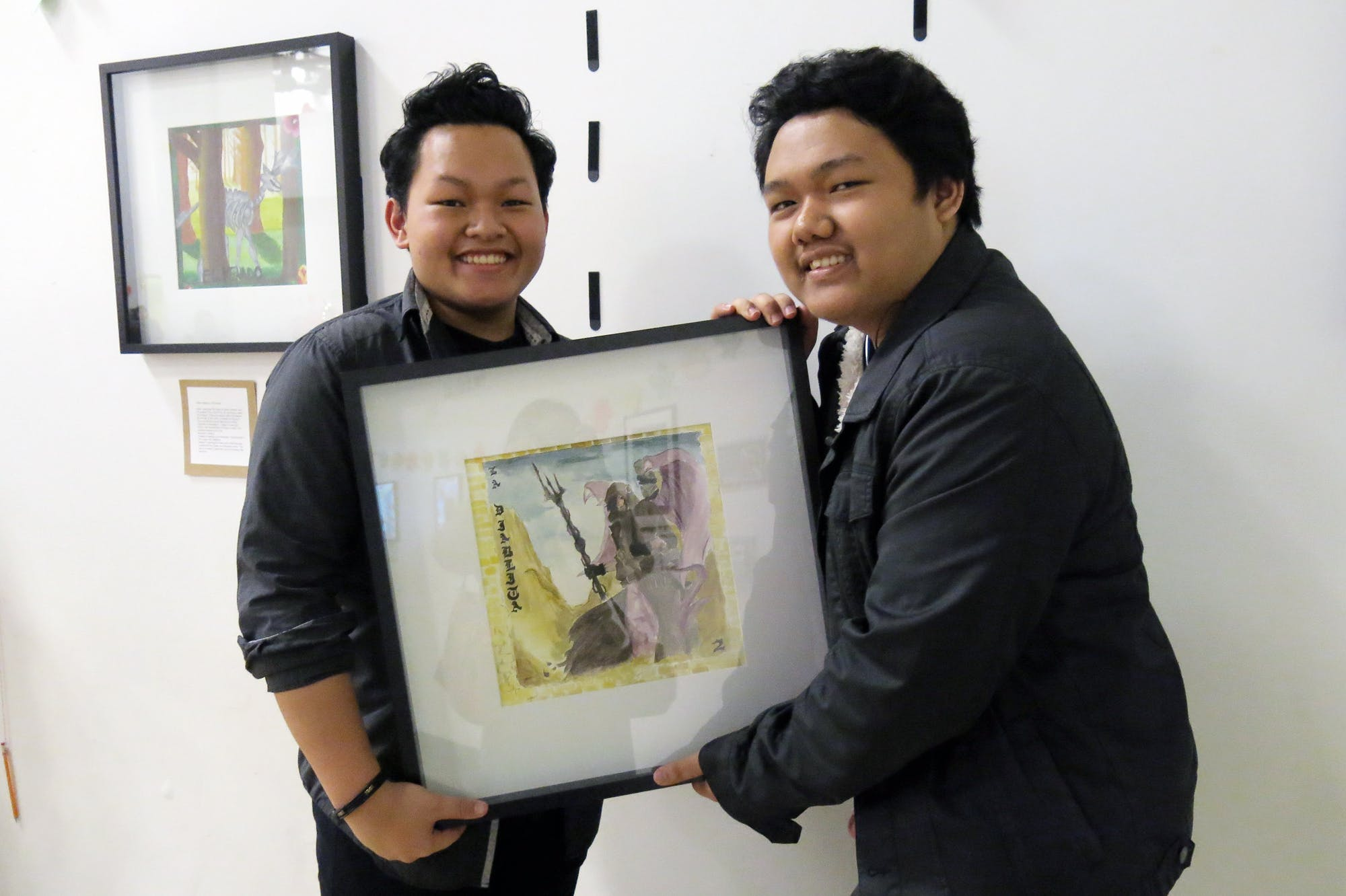 Jeremiah Borbe, a junior at UCLA Community School, helped his brother Joshua, a senior, to display his artwork at the 4th Art Auction.
