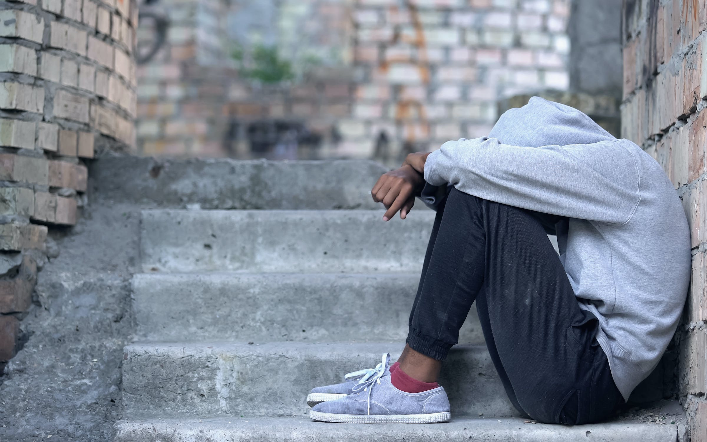 Young black student sitting on staircase with head in between knees