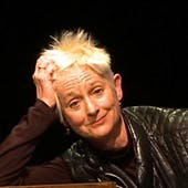 Susan Leigh Foster, a white woman with short, spiky white hair, leans her head on the palm of her right hand, with a bemused expression on her face.